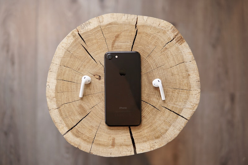 Black iPhone and airpods placed on a tree stump, depicting podcasts.