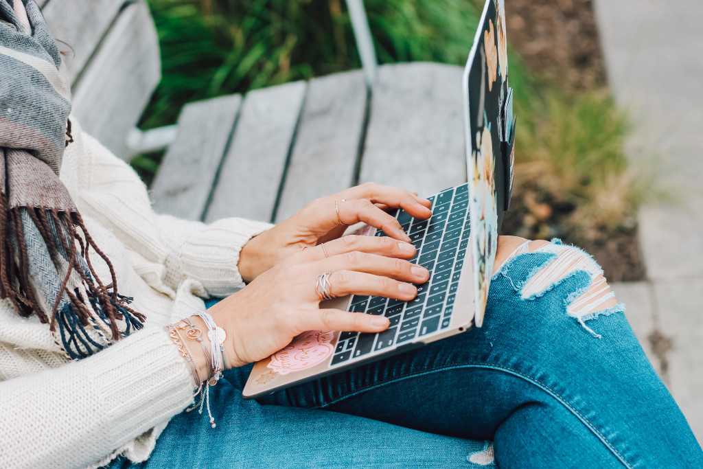 Close up of hands on laptop, woman sitting on park bench in nature.